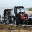 Firefighters stand by after extinguishing a tractor and stubble fire in a Waiwera South paddock...
