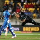 Scott Kuggeleijn of New Zealand bowls while Shikhar Dhawan of India looks on during game one of...