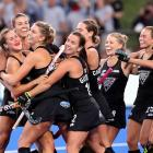 Olivia Merry (left), of New Zealand, is congratulated by team-mates after scoring a goal during...
