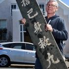 Property owner Mark Thom holds a board understood to be more than 100 years old, found at a...