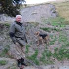 Lawrence sheep and beef farmer Dave Robertson surveys one of the many slips that occurred on his...