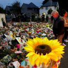 People pay their respects to the victims of Friday's shooting, in front of the Al Noor mosque in...