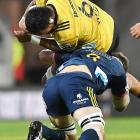 Hurricanes loose forward Vaea Fifita is tackled by Highlanders co-captain Luke  Whitelock in the...