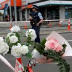 A police officer stands near a floral tribute left at a cordon at an intersection near the...