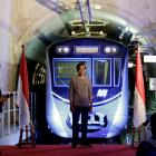 Indonesian President Joko Widodo (C) in front of a Jakarta Mass Rapid Transit train during the...