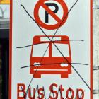 A logo and wording on a former bus stop sign have been crossed out.