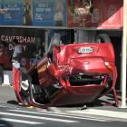 A car lies on its roof in Caversham yesterday, after being rear-ended by a van while stopped at a...