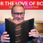 University of Otago special collections librarian Donald Kerr holds an old Latin book, which is...