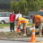Wanaka residents Loris King (left) and Liz Hall watch as Fulton Hogan kerb and channel operations...