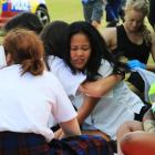 St Kevin's College year 11 pupil Leyanne Monoy (14) is comforted as she takes part in an...