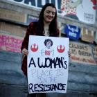 A woman holds a banner during a gathering to mark International Women's Day in Lisbon, Portugal....