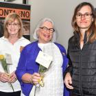 (from left) Lyn Herbert, Lyn Farry and Lynette Grave give Iloma Mollison a yellow rose yesterday...
