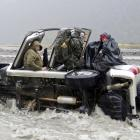 Four cold and wet passengers in a 4WD await rescue from the flooding Hopkins River on Saturday