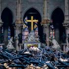 A view of the cross and sculpture of Pieta by Nicolas Coustou in the background of debris inside...
