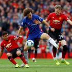 Chelsea's David Luiz (C) battles through the Manchester United defence. Photo: Reuters