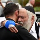 Rabbi Yisroel Goldstein (R) is hugged as he leaves a news conference at the Chabad of Poway...