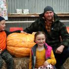 Hamish Wilson (right) won the title for largest pumpkin grown by an adult. He is pictured with...