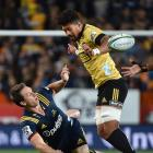 The Highlanders' Ben Smith is tackled by Hurricanes lock James Blackwell while Hurricanes flanker...