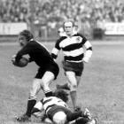 New Zealand's Bob Burgess (left) looks to pass the ball as he is tackled in a match against the...