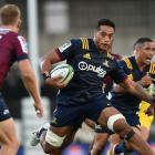 Highlanders flanker Shannon Frizzell looks to step Reds fullback Bryce Hegarty in the teams'...