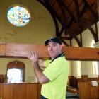 Kris Shaw, of the South Island Organ Company, removes an oak and mahogany organ pipe from the...