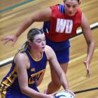Physed B midcourter Becky Paterson looks to move the ball on while Ainsley McGrath, of Physed...