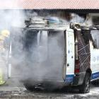 Members of the Wanaka Volunteer Fire Brigade work to put out a Wanaka Solar van that caught fire...