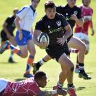 New Zealand Universities first five-eighth Tyler Campbell goes past Kansai Universities centre...