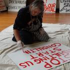 Gillian Bartrum paints a placard in preparation for tomorrow's Waitaki Community Hospital Action...