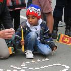Chathuska Pitiwila Liyanage (6), of Oamaru, lights candles at a vigil for the 359 people killed...