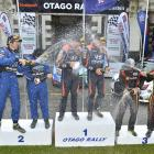 Otago Rally winners Hayden Paddon and John Kennard are sprayed by Ben Hunt and Tony Rawstorn ...