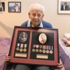 Russell Towns holds a framed display of medals won by his father Alfred in World War 1 and by him...