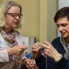 Dunedin Supergrans' Jessie Sutton gives some knitting tips to University of Otago student and...