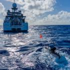 The submarine DSV Limiting Factor floats near the research vessel DSSV Pressure Drop above the...