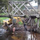 Otago Regional Council contractors remove a log from the Sir Truby King bridge in Tahakopa...