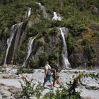 Tourists walk past waterfalls at the Franz Josef Glacier in summer. Photo: AP
