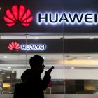 A pedestrian talks on the phone while walking past a Huawei Technologies Co. store on January 29,...