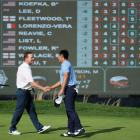 Danny Lee (R) shakes hands with Justin Bertsch on the 18th green at the end of the first round....