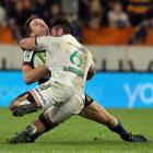 Highlanders fullback Ben Smith loses his footing and slips in to the tackle of Chiefs loose...