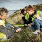 Scientist Hiltrun Ratz (left) and tour guides Julien Arriaga and Brooke Davies inspect a blue...