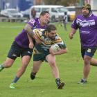 Cooks player Lionel Tuwairua is tackled by South Pacific Raiders player James Piho, with Andrew...