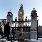 Melting snow is seen as workers pass Big Ben in Westminster in London. Londoners are still facing...