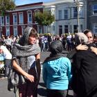 Members of the public and members of Dunedin's Al Huda mosque embrace as hundreds of others...