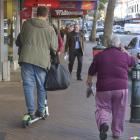 Weaving between pedestrians, a Lime scooter rider makes his way down George St using the footpath...