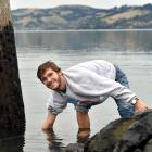 Fox Meyer (21) adjusts a sensor in Otago Harbour that allows him to monitor water flows.  Photo:...