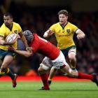 Australia's Kurtley Beale is tackled by Wales' Dan Lydiate as Michael Hooper comes in support....