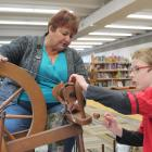 Lynette Jack shows Tyrone McLeod (9) how to use a spinning wheel. PHOTO: LUISA GIRAO