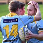 University centre Matt Faddes celebrates scoring a try with team-mates Patrick Atkinson (left)...