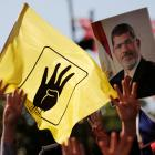 People flash Rabia signs as they hold a picture of former Egyptian president Mursi during a...