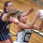 Columba College wing defence Olivia Fowler (right) takes the ball ahead of St Hilda's wing attack...